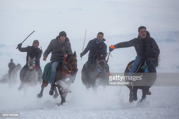 Men take part in a horse race across the frozen Cildir Lake during the Cildir Lake Golden Horse Festival on February 4 2017 in Cildir Turkey The...