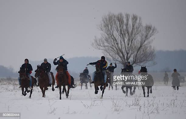 Men take part in a horse race during the traditional Epiphany celebration in the village of Pietrosani southeast of Sibiu Romania on January 6 2016...