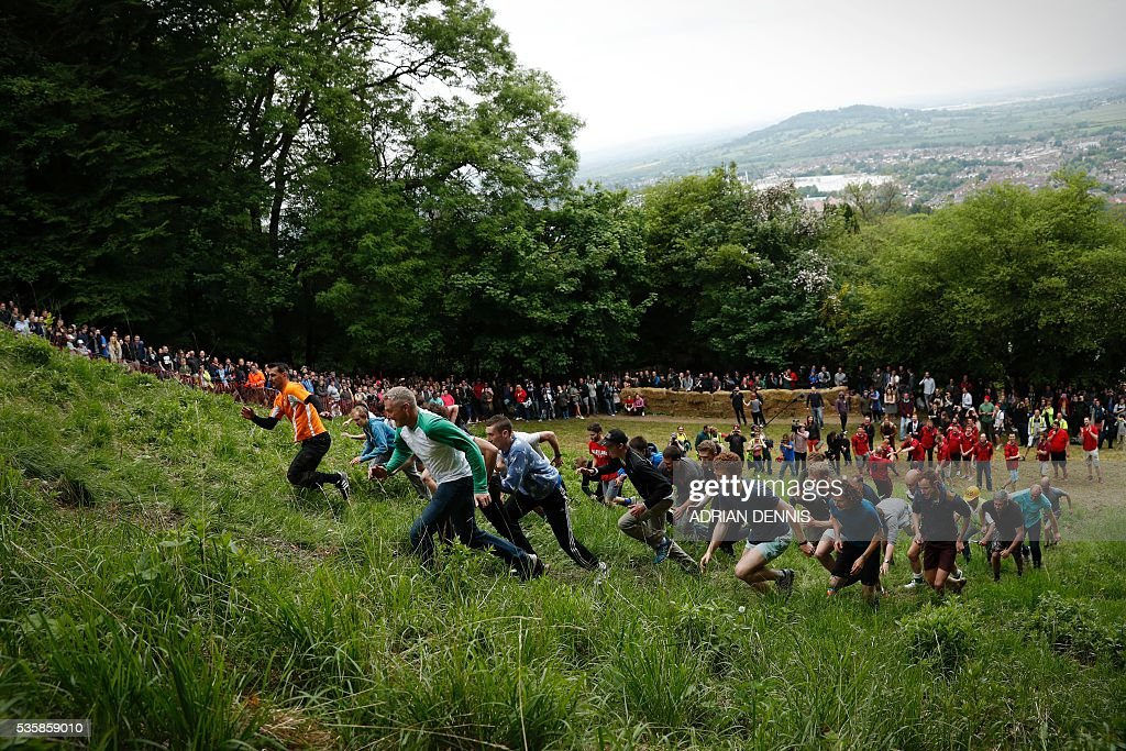 Men take part in an uphill race during the annual Cooper's Hill cheese rolling competition near the village of Brockworth, Gloucester, in western England, on May 30, 2016. The annual Cooper's Hill Cheese Rolling involves hordes of fearless competitors chasing an eight pound Double Gloucester cheese down a steep hill. The slope has a gradient in places of 1-in-2 and in others 1-in-1, its surface is very rough and uneven and it is almost impossible to remain on foot for the descent. The winner of the downhill race wins the cheese. / AFP / ADRIAN