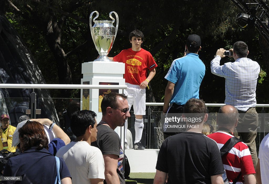 Men take pictures of the UEFA Champions League Cup on display at the Retiro Park in Madrid on May 21, 2010 ahead of the UEFA Champions League final. Inter Milan will face Bayern Munich for the UEFA Champions League final match to be played at the Santiago Bernabeu Stadium in Madrid on May 22, 2010.