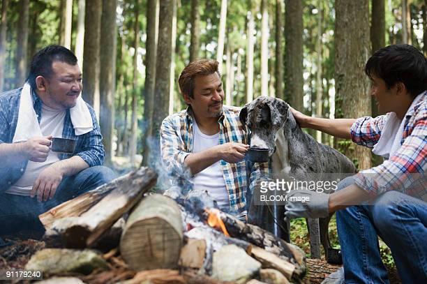 Men taking rest by bonfire
