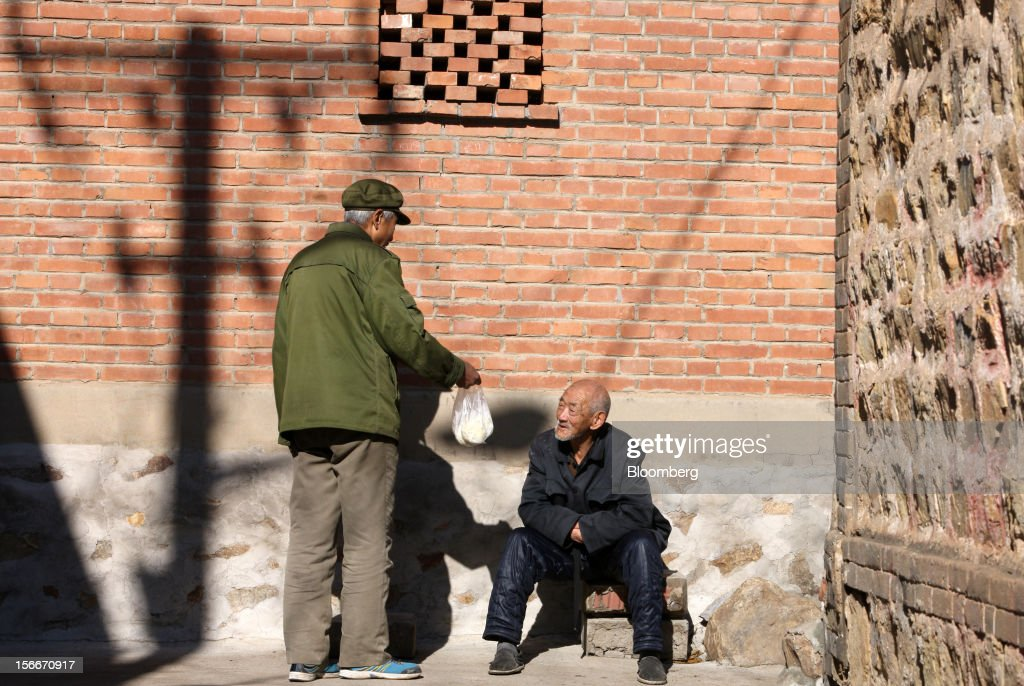 Men talk in front of a house in Pinggu, on the outskirts of Beijing, China, on Saturday, Nov. 17, 2012. China's gross domestic product slowed to 7.4 percent in the July-September period from a year earlier, the weakest in three years. Photographer: Tomohiro Ohsumi/Bloomberg via Getty Images