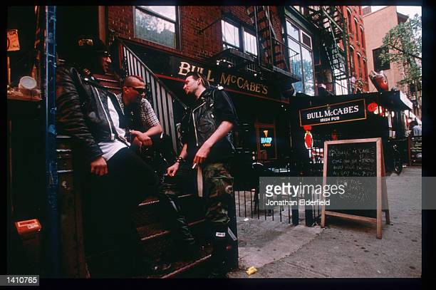 Men talk outside a pub on St Mark''s Place between Second and Third Avenue in the East Village June 1 1998 in New York City Populated by residents of...