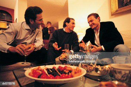 Men Talking at a Social Gathering : Stock Photo