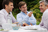 Men talking at outdoor meal