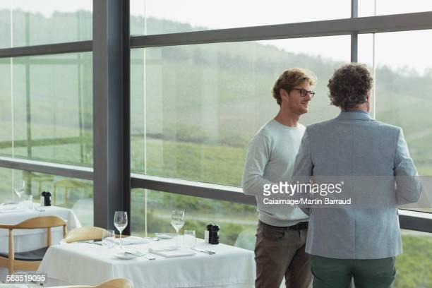Men talking at winery dining room window