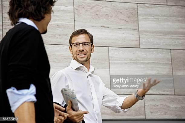 Men talking, holding a newspaper