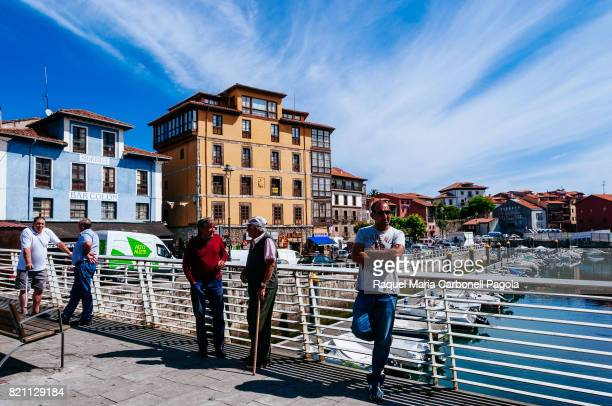 Men talking on a bridge with boats moored at harbor and village houses at back