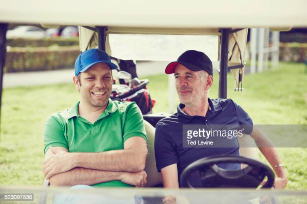 Men talking on golf cart