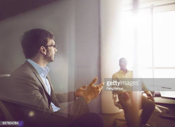 Men talking together in business office meeting