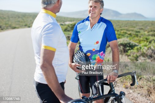 Men talking with bicycles in remote area : Stock Photo