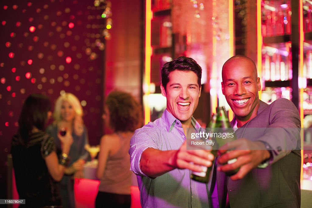 Men toasting beer bottles in nightclub : Stock Photo