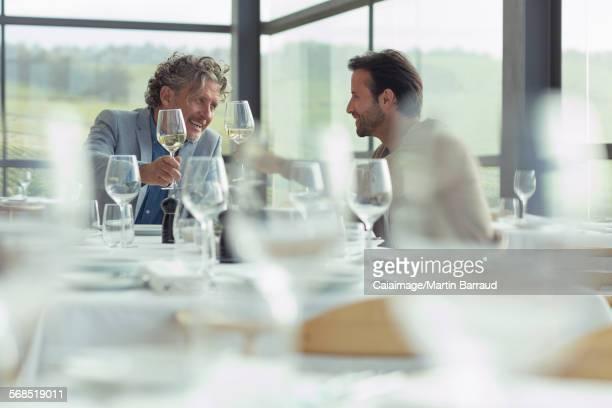 Men toasting wine glasses at restaurant table