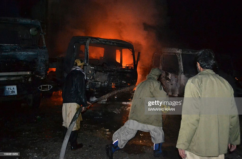 Men try to extinguish burning NATO supply truck in Quetta on January 11, 2013, after unidentified men fired rockets on NATO containers carrying goods for international troops operating in Afghanistan, killing one person and destroying at least five vehicles in the Hazar Ganji area on the outskirts of Quetta on Friday. Banaras KHAN
