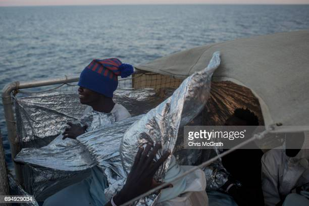 Men try to shelter from the wind onboard the Migrant Offshore Aid Station Phoenix vessel enroute to Italy on June 11 2017 off Catania Italy An...