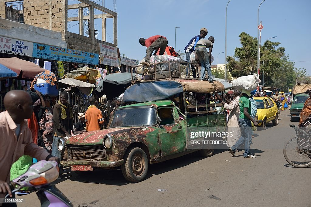 Men unload a Peugeot 404 pick-up used as a taxi on January 21, 2013 in a street of Bamako. French and Malian troops recaptured the key towns of Diabaly and Douentza on Monday in a major boost in their drive to rout Al Qaeda-linked rebels holding Mali's vast arid north. AFP/PHOTO ERIC FEFERBERG