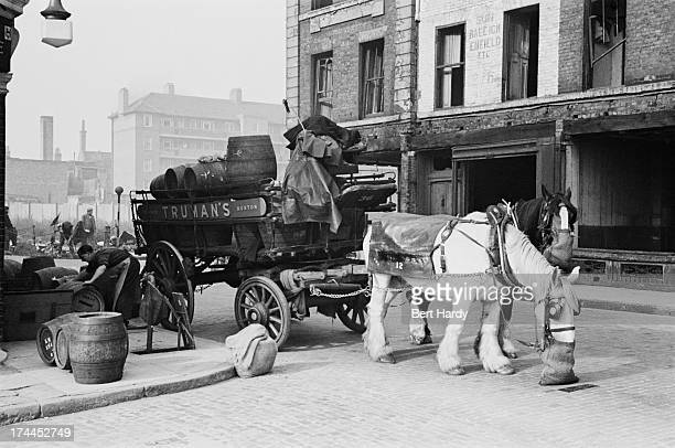 Men unloading barrels of beer outside a pub in the Pool of London while their carthorse feeds from a nosebag December 1949 Original publication...