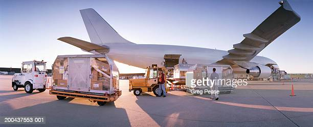 Men unloading cargo plane, sunset