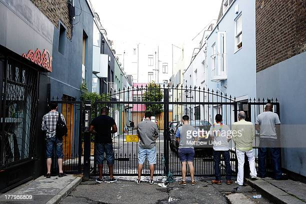 Men urinate on the gates of a mews street during the Notting Hill Carnival on August 26 2013 in London England More than one million people are...