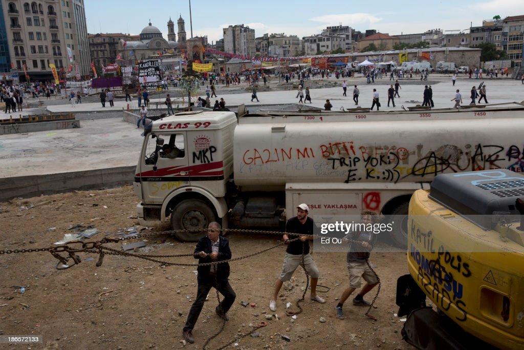 Men use chains to pull down police barricades from Taksim Square in Istanbul Turkey on June 6 2013 Refusing to yield to a week of protests in dozens...