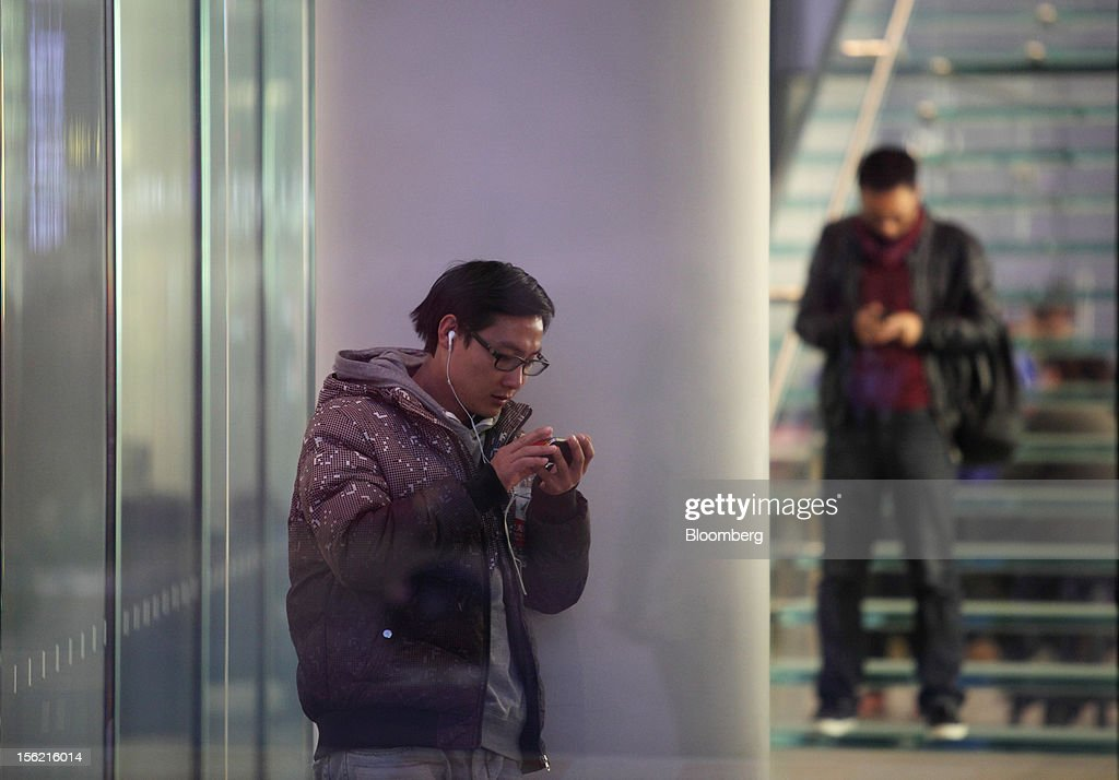 Men use smartphones in the Sanlitun area of Beijing, China, on Friday, Nov. 9, 2012. China's retail sales exceeded forecasts and inflation unexpectedly cooled to the slowest pace in 33 months, signaling the government is boosting growth without driving a rebound in prices. Photographer: Tomohiro Ohsumi/Bloomberg via Getty Images