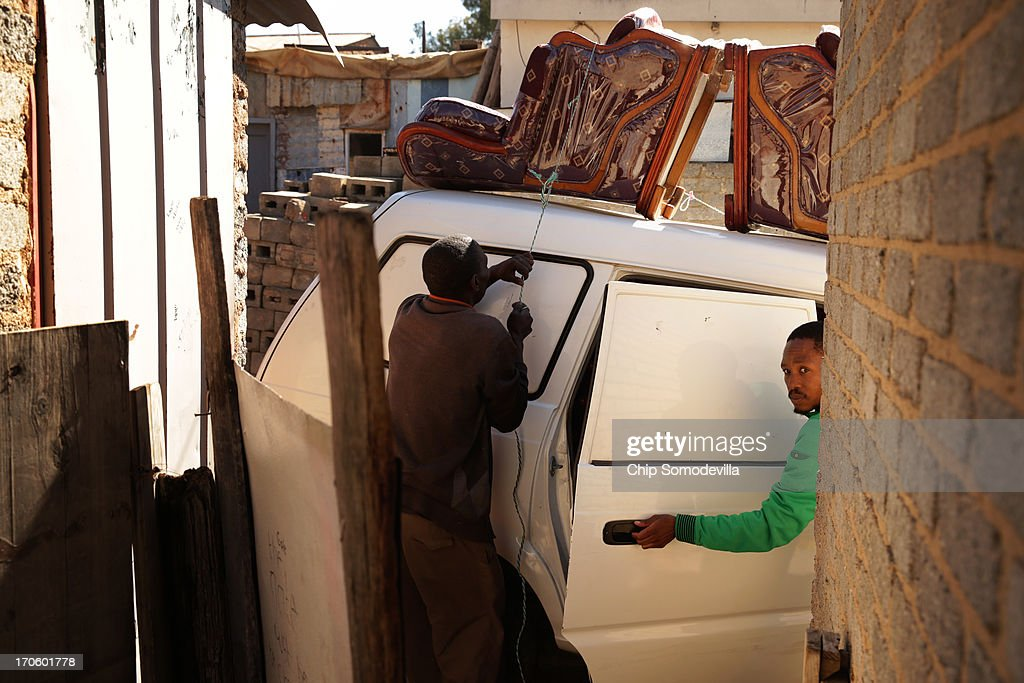 Men use string to secure furniture to the room of a van in the Alexandra Township around the corner from where former South African President Nelson Mandela lived in the 1940s June 15, 2013 in Johannesburg, South Africa. A leader of the anti-apartheid movement and the first democratically elected president of South Africa, Mandela is spending a seventh night in hospital and is reported to be responding better to treatment for a recurring lung infection.