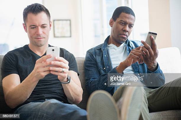Men using cell phones on sofa