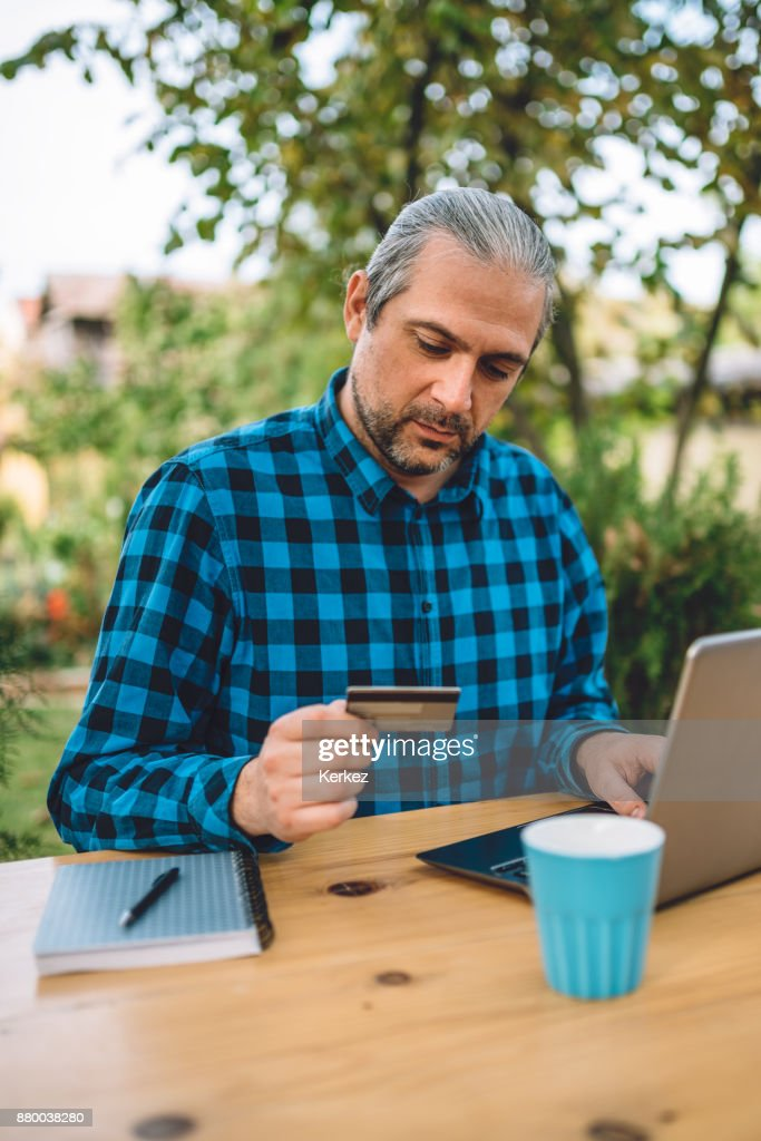 Men Using Credit Card At Backyard Patio : Stock Photo