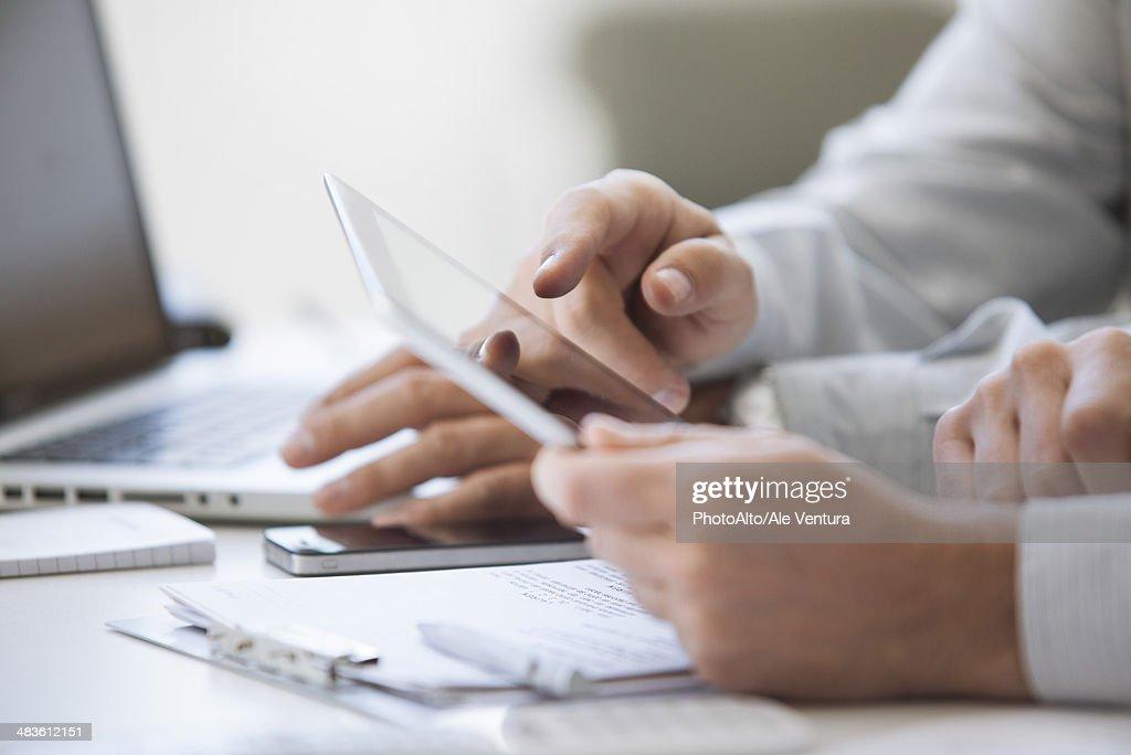 Men using digital tablet, cropped