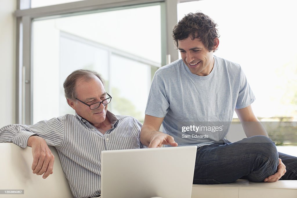Men using laptop together : Stock Photo