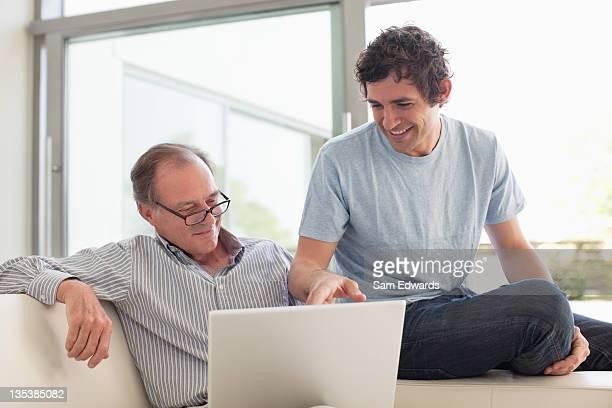Men using laptop together