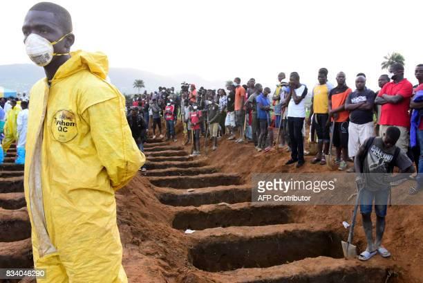 Men wait beside empty graves for the coffins of mudslide victims on August 17 2017 at Waterloo cemetery near Freetown Sierra Leone Sierra Leone...