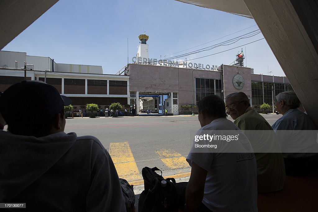 Men wait for a bus across the street from the Grupo Modelo SAB brewery in Mexico City, Mexico, on Thursday, June 6, 2013. Heineken NV and Grupo Modelo SAB, the dominant brewers in Mexico with brands such as Dos Equis and Corona, are nearing the end of an almost three-year-old government antitrust probe. Photographer: Susana Gonzalez/Bloomberg via Getty Images