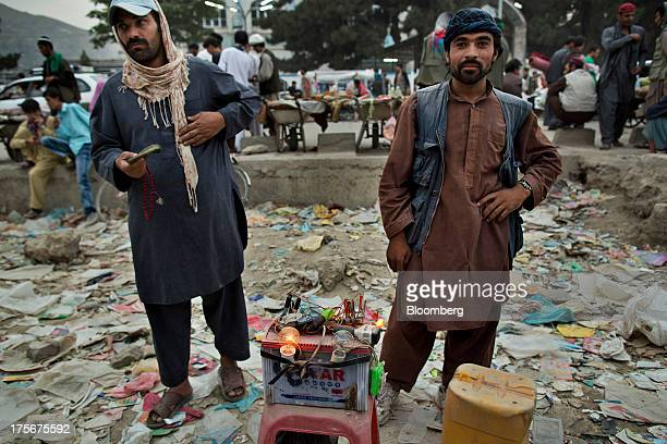 Men wait for customers at their mobile phone charging station in downtown Kabul Afghanistan on Saturday Aug 3 2013 A smooth US exit from Afghanistan...
