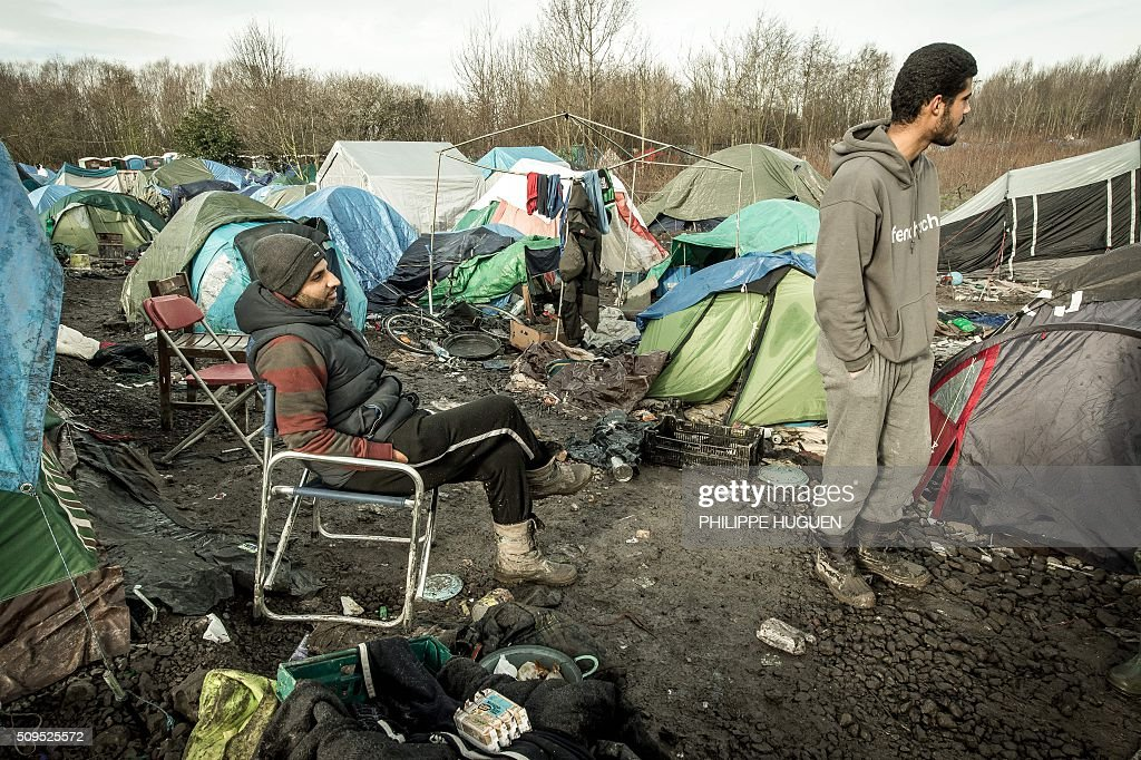 Men wait in the so-called 'Jungle' migrant camp in Gande-Synthe where 2,500 refugees from Kurdistan, Iraq and Syria live on February 11, 2016 in Grande-Synthe near the city of Dunkirk, northern France. / AFP / PHILIPPE HUGUEN