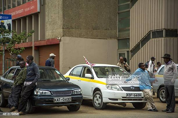 Men wait next to taxis adorned with US flags on July 25 2015 in Nairobi US President Barack Obama arrived in Kenya on the July 25 as part of a...