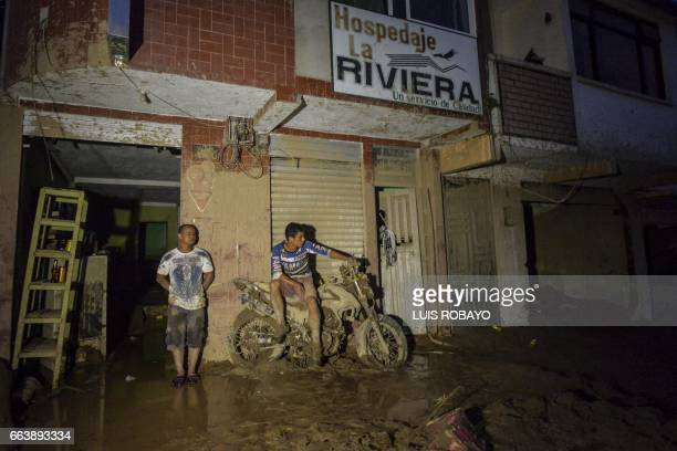 TOPSHOT Men wait outside their home which was damaged by mudslides following heavy rains in Mocoa Putumayo department southern Colombia on April 2...