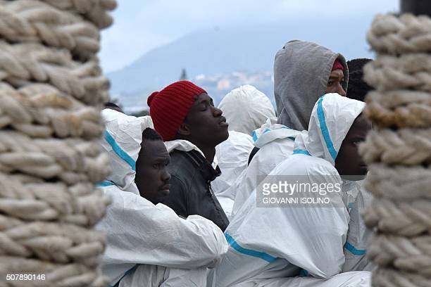 TOPSHOT Men wait to disembark from the Italian Coast Guard vessel 'Dattilo' following a rescue operation of migrants and refugees at sea on February...