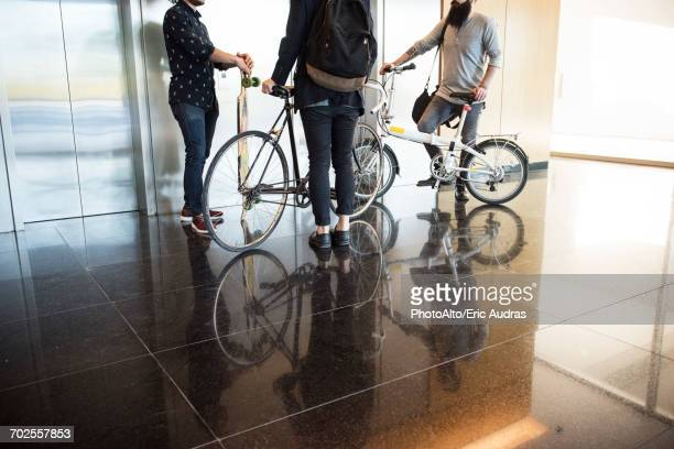 Men waiting for elevator with bicycles and longboard, low section
