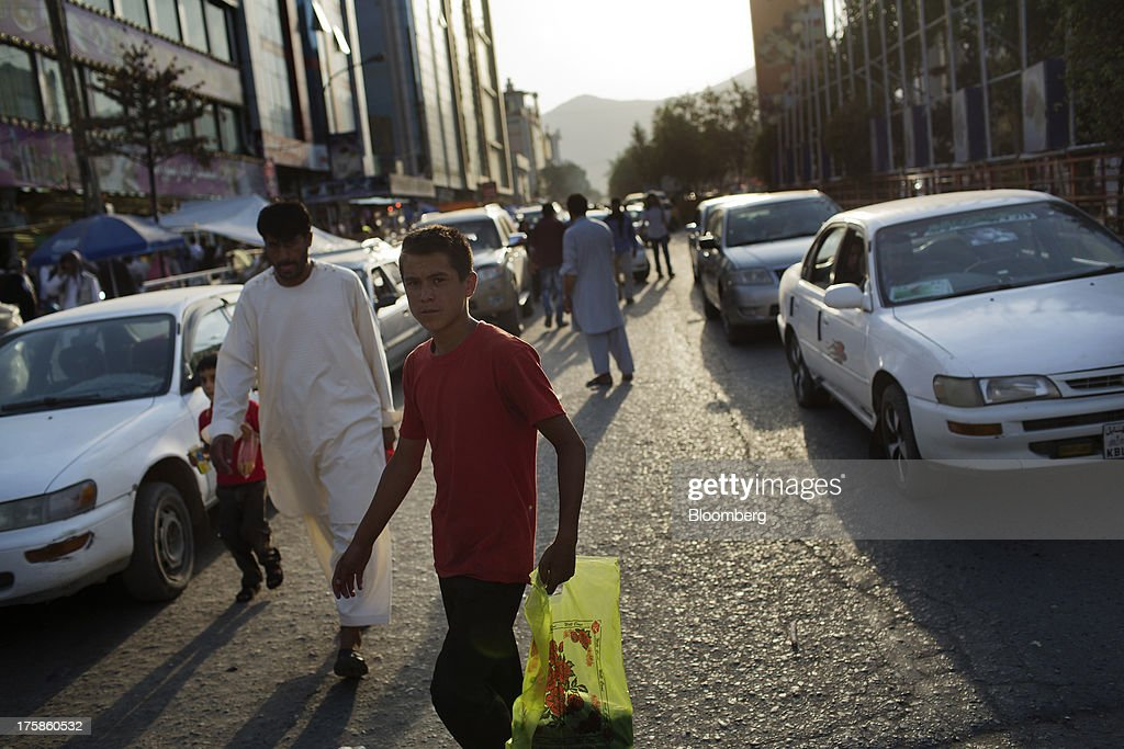 Men walk along a street in Kabul, Afghanistan, Wednesday, Aug. 7, 2013. A smooth U.S. exit from Afghanistan will depend on Pakistans cooperation with the logistical pullout, as well as its backing for peace talks in neighboring Afghanistan and an end to any support for extremist proxies operating there. Photographer: Victor J. Blue/Bloomberg via Getty Images