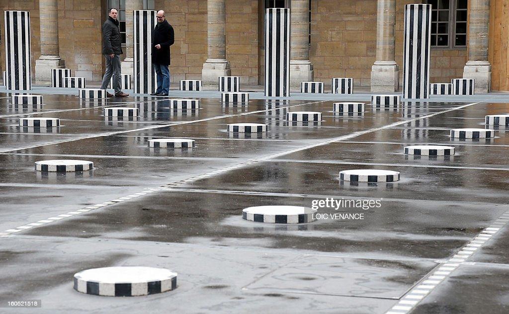 Men walk between Buren columns at the Palais Royal in Paris on February 2, 2013.