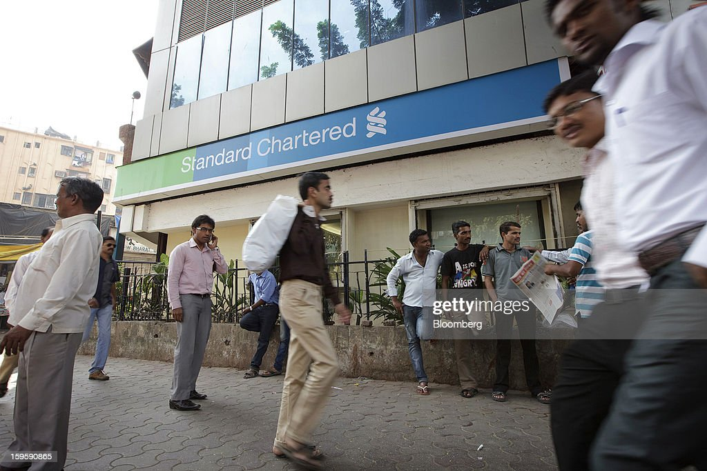 Men walk by a Standard Chartered Plc bank branch in Mumbai, India, on Wednesday, Jan. 16, 2013. India's financial system has been made vulnerable by a deterioration in bank assets and a lack of capital as the economy slowed, according to the International Monetary Fund. Photographer: Kuni Takahashi/Bloomberg via Getty Images