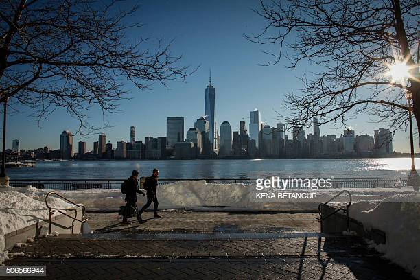 Men walk by the Hudson River Shore as the New York Skyline it's seen from Exchange Place on January 24 2016 in Jersey City A massive blizzard that...