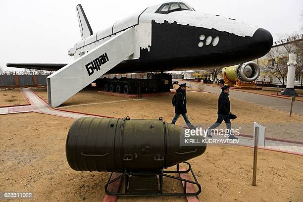 Men walk close to one of the Soviet era space shuttles Buran installed in a museum at Russianleased Baikonur cosmodrome in Kazakhstan on November 15...
