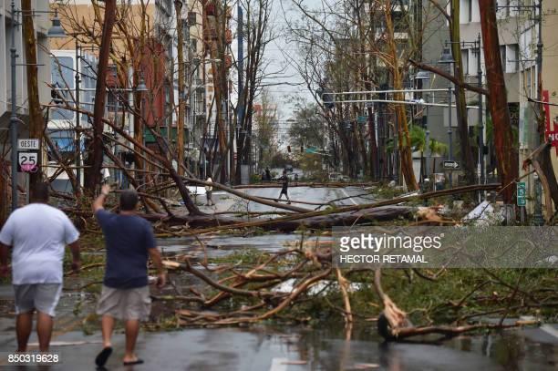 TOPSHOT Men walk damaged trees after the passage of Hurricane Maria in San Juan Puerto Rico on September 20 2017 Maria slammed into Puerto Rico on...