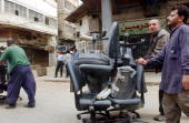 Men walk down a street with looted chairs April 13 2003 in Baghdad Iraq The Iraqi capital Baghdad is still reeling from widespread looting and...