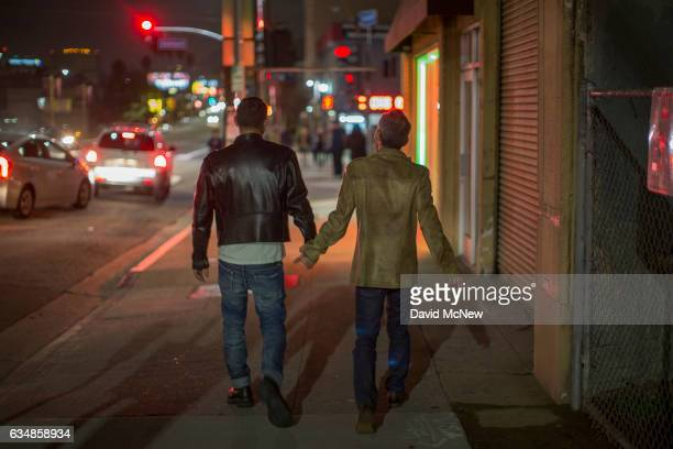 Men walk handinhand down Sunset Boulevard during a rally to mark the 50th anniversary of the protest at The Black Cat Tavern credited as the site of...
