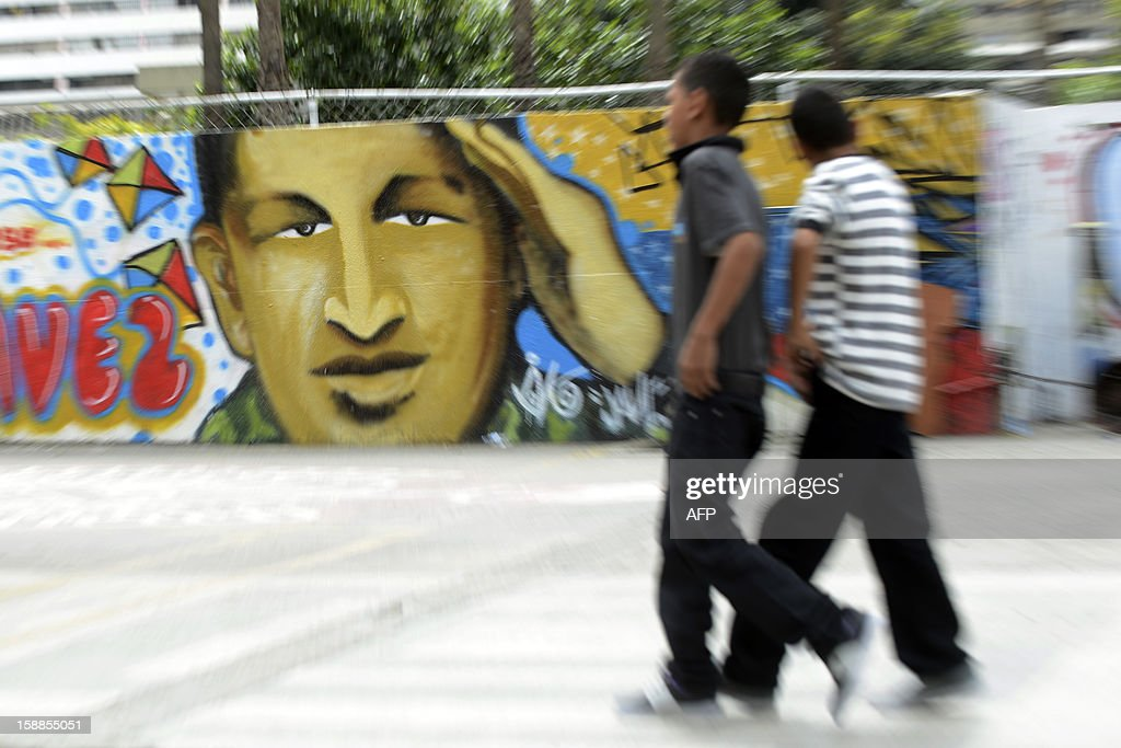Men walk near a mural of Venezuelan President Hugo Chavez in Caracas, were the streets are practically deserted, on January 1, 2013. Somber Venezuelans began 2013 fretting over their ubiquitous and garrulous leader Hugo Chavez, wondering what the future holds as the president wages a tough battle with cancer in a Havana hospital. New Year's Eve revelry was tempered, and official acts -- two open air concerts -- were canceled outright out of respect for the ex-paratrooper who has dominated this oil-rich country so thoroughly since taking power in 1999. Chavez underwent his fourth cancer-related surgery three weeks ago in Havana and has been bed-ridden ever since. Information on his condition is scant, with the government admitting only to 'complications' in his recovery. AFP PHOTO/LEO RAMIREZ