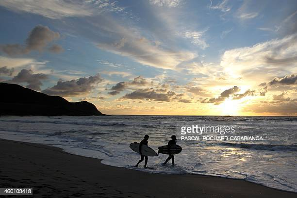 Men walk on the beach after surfing at Capo di Feno beach on December 7 in Ajaccio on the French Mediterranean island of Corsica AFP PHOTO / PASCAL...