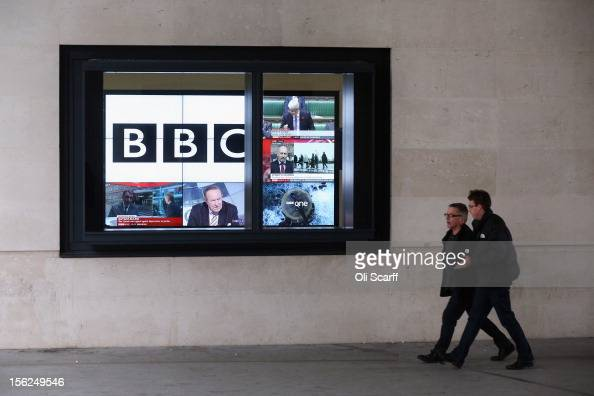Men walk past a bank of television screens displaying BBC channels in the BBC headquarters at New Broadcasting House on November 12 2012 in London...